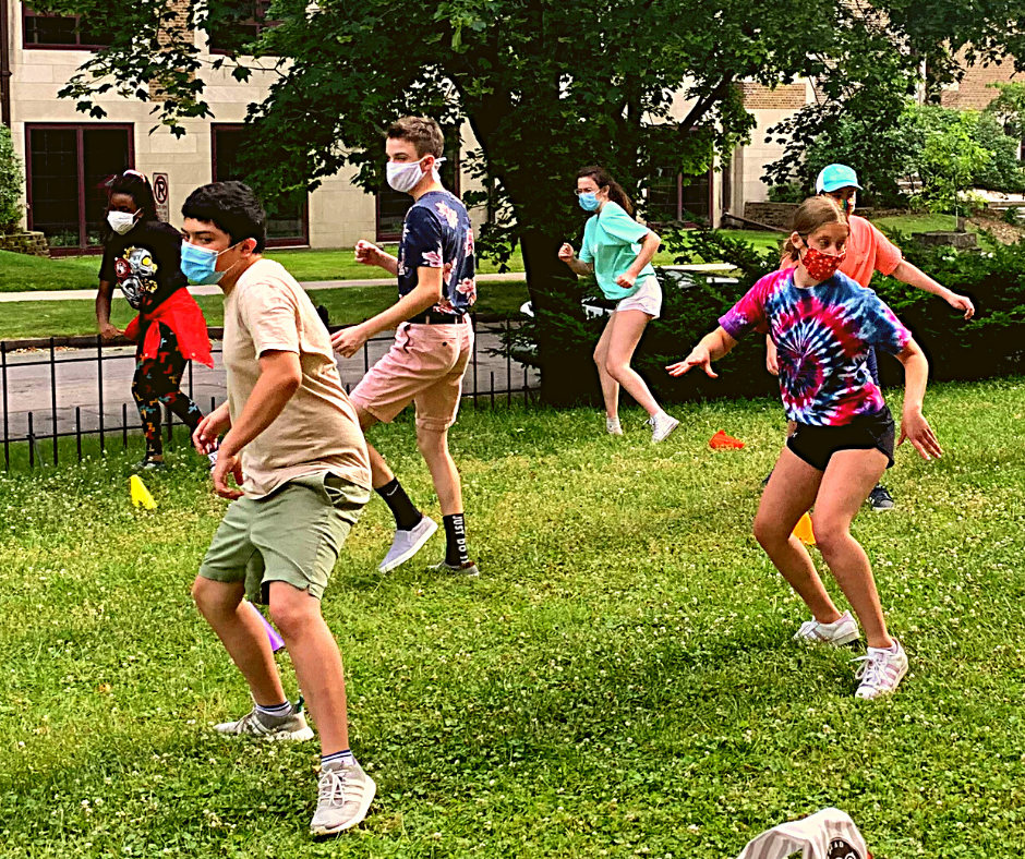 Teens in masks rehearse a choreographed dance on a lawn