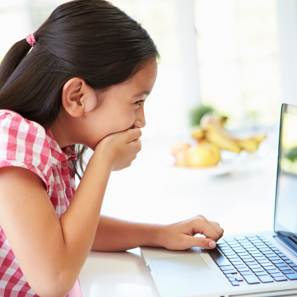 A laughing girl covers her mouth with her hand as she looks at a laptop screen