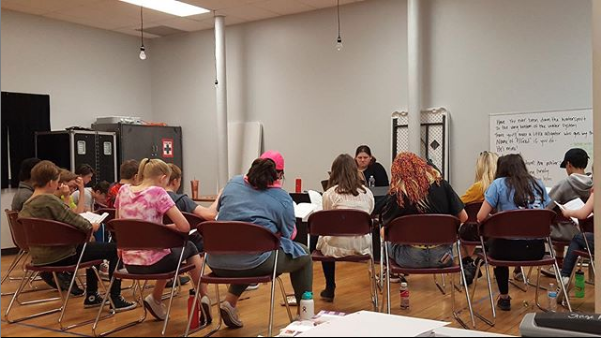 Teens sit in a half-circle with backs facing in SteppingStone's Ecolab Studio