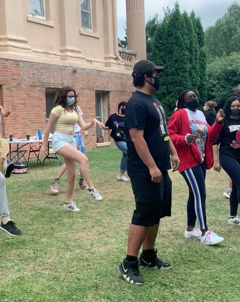 Teens wearing masks rehearse a synchronized dance