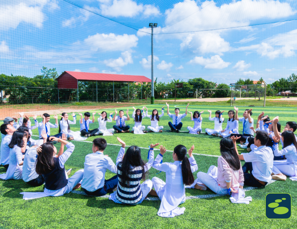 teens sit in a circle on an athletic field with their arms raised to toward the sky