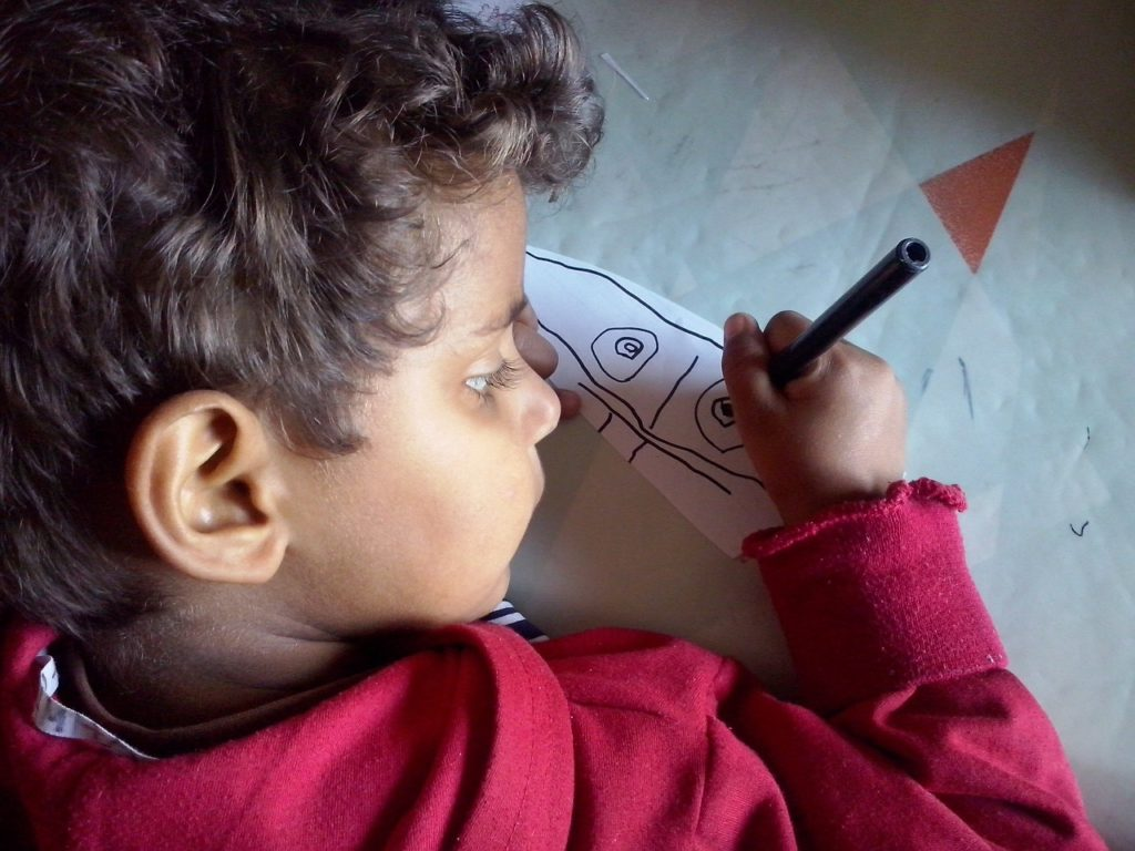 a young child draws with a marker on a white piece of paper