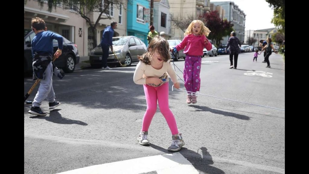 a young girl bends over laughing while holding a jump rope in a street.