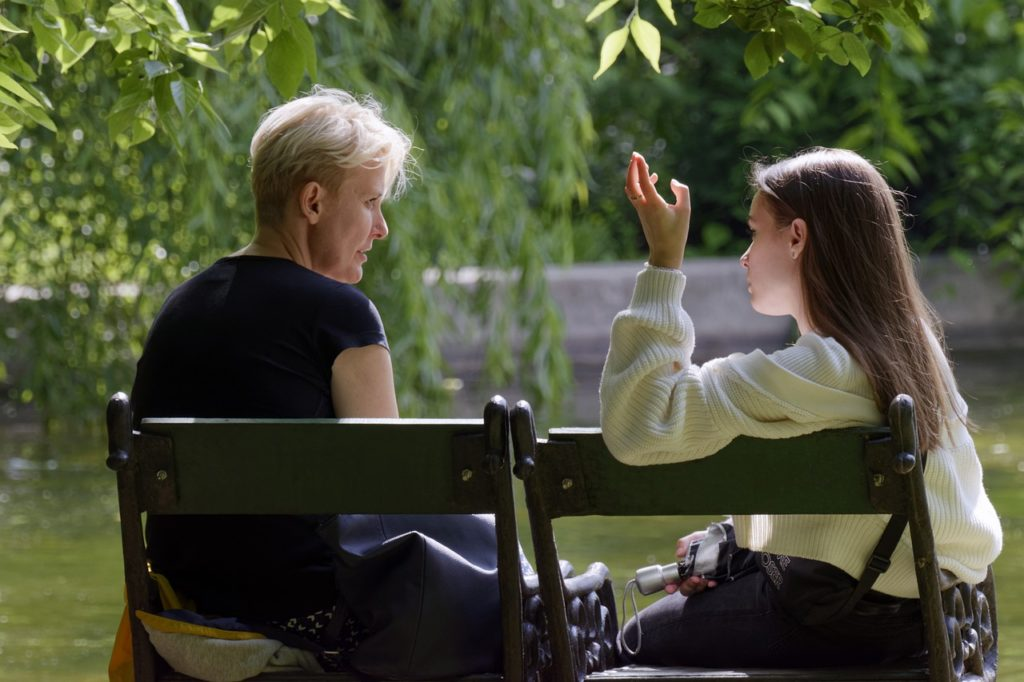 a teen talks to an adult on a folded chair under a willow tree by a river