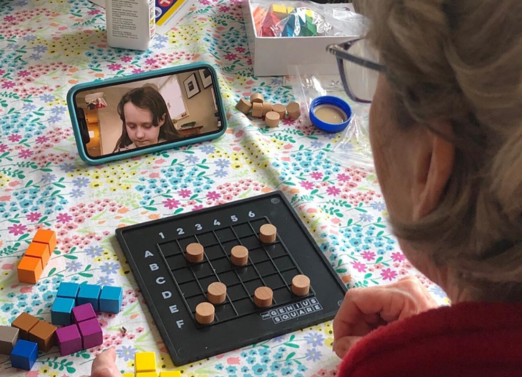 An older adult plays a board game via video conference with a child