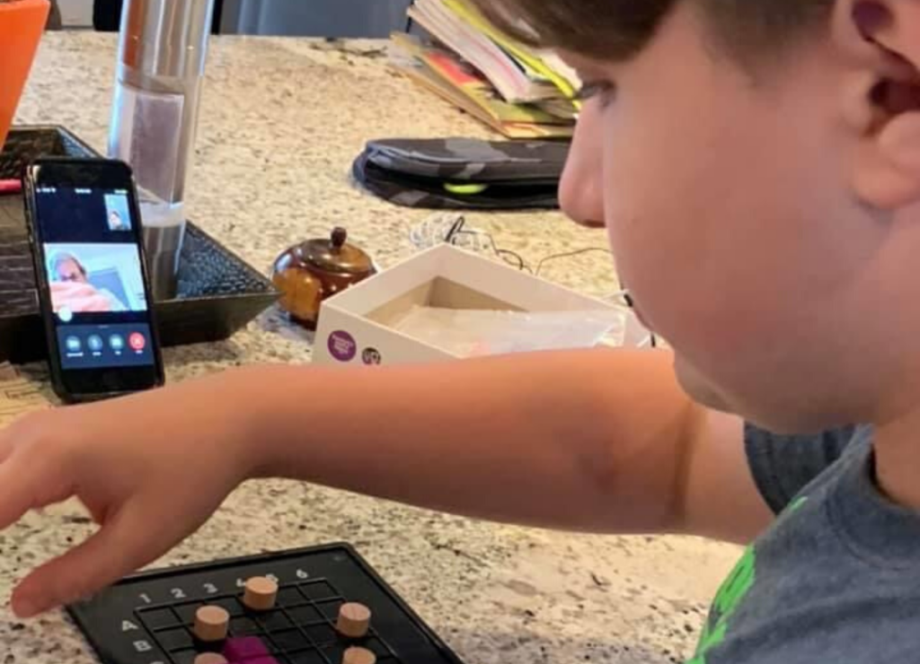 A child plays a board game over video chat with an older adult