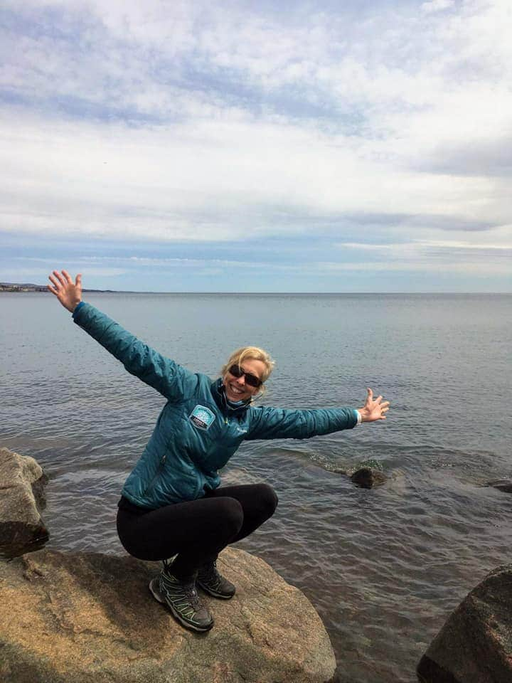 Bonnie Carlson-Green crouches with arms outstretched on a rock jutting into a large lake