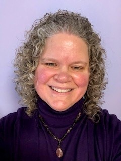 Picuture of a smiling woman with curly light gray hair and a purple turtleneck.
