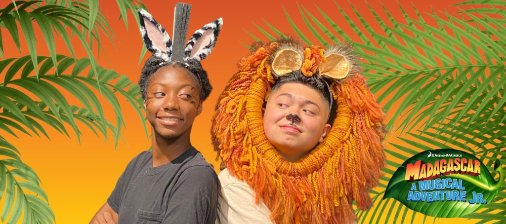 Two young people, one is wearing zebra ears and the other has a lion's mane.